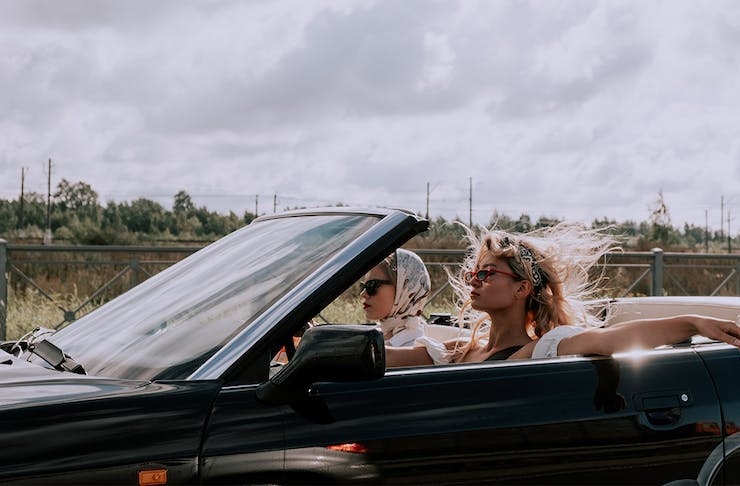two women drive a convertible with the top down.