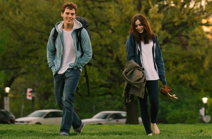 a young man and woman laugh while walking across a park