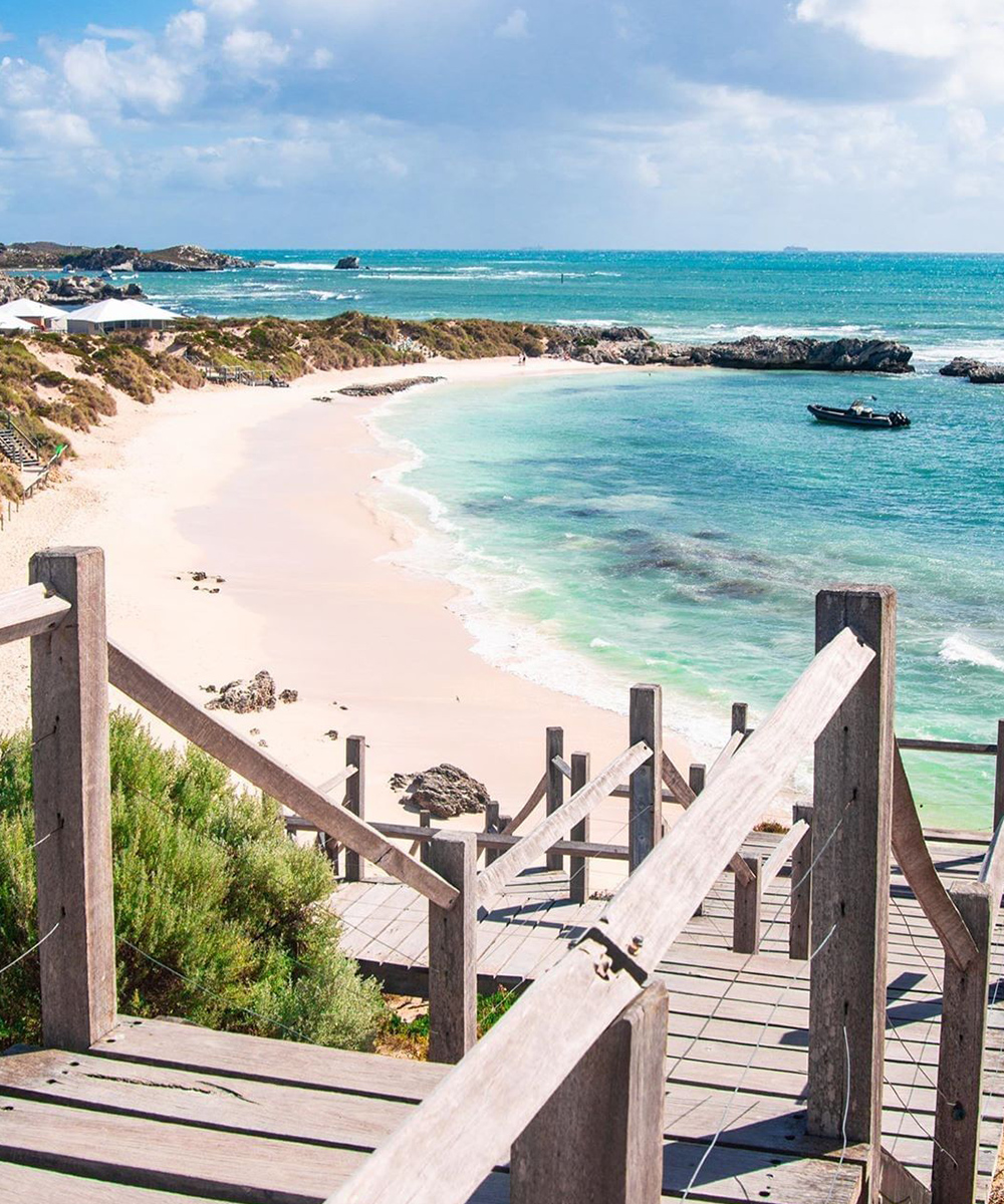 A stunning vista of Pinky Beach at Rottnest Island with white sand, azure water and a blue sky.