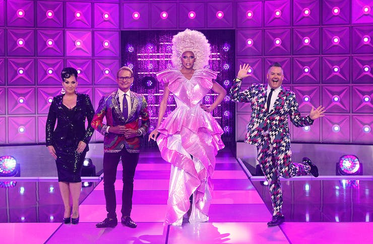 Rupaul and their fellow judges pose on a purple stage
