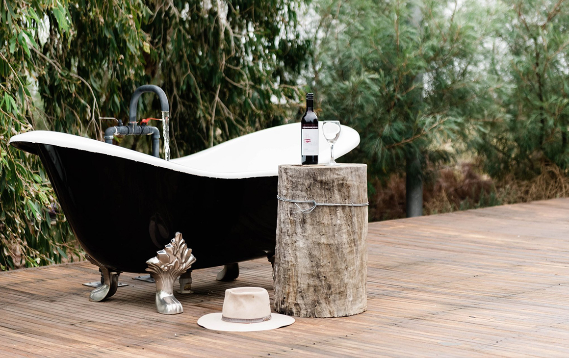 outdoor bath with a bottle of wine