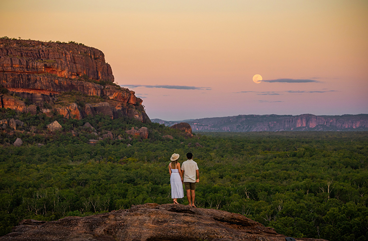 two people standing on rock in the northern territory with a full moon