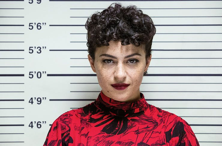 a woman with dark red lipstick poses for a mug shot.