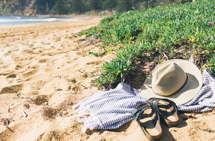 sandals, towel and beach bag on beach