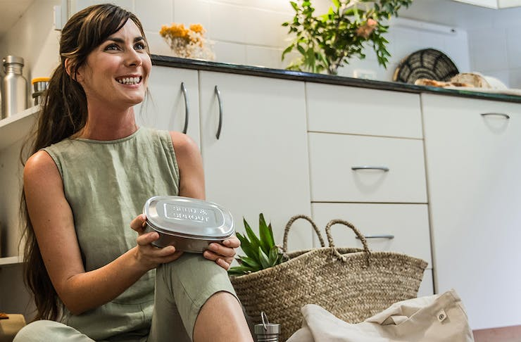 Seed & Sprout founder Sophie Kovic sits on the floor of a kitchen smiling, while holding her products in it.