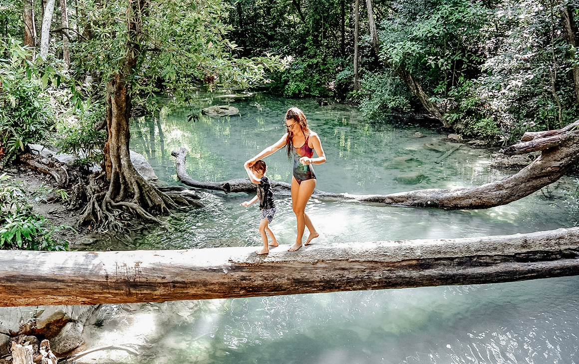 A woman and her young son walks across a fallen tree trunk that lies across a beautiful flowing creek.