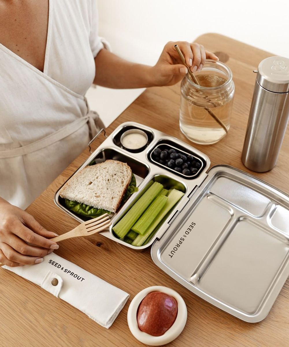 a stainless steel lunch box filled with a sandwich and healthy treats sits open on a wooden table.