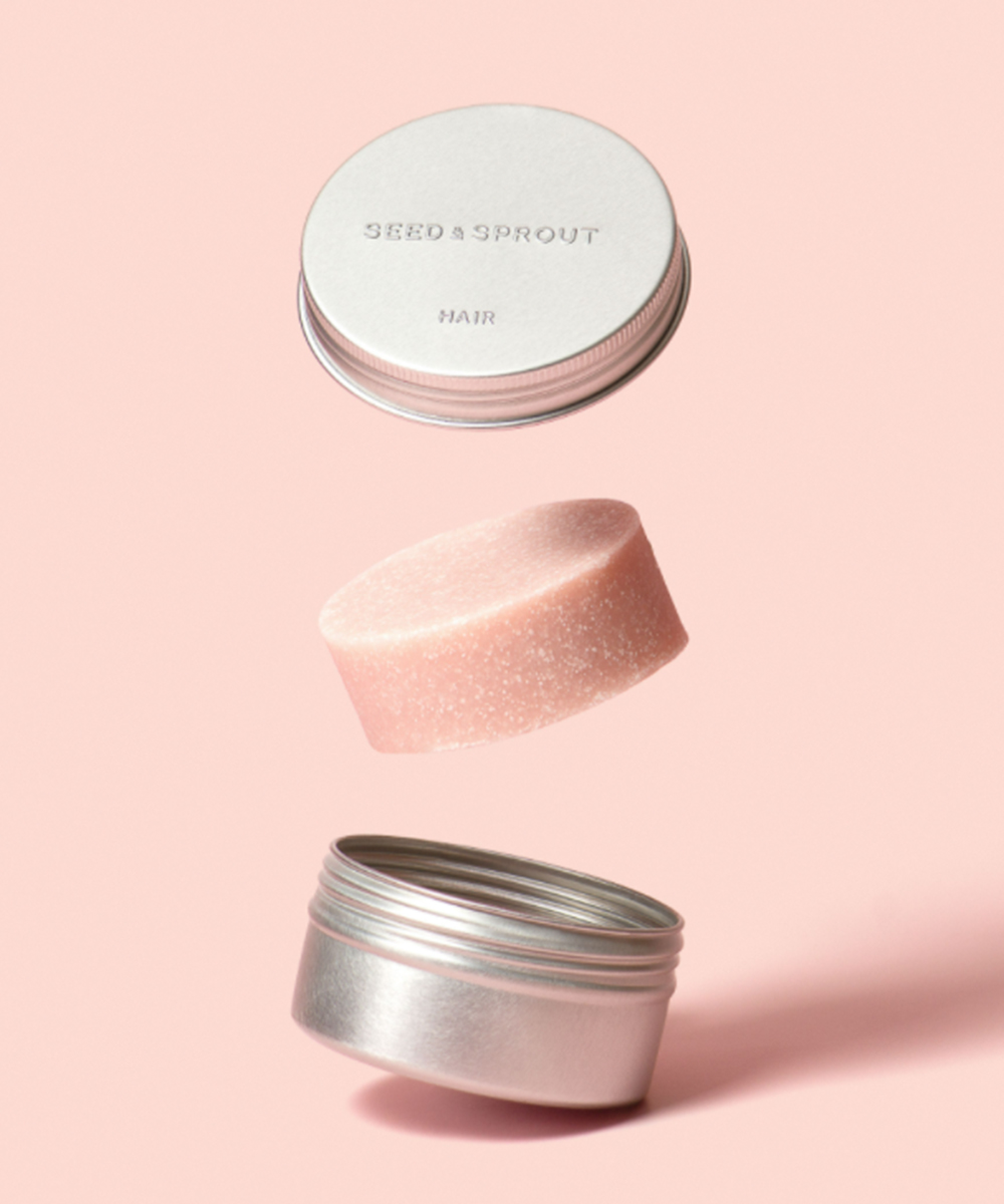 an open tin with a pale pink shampoo bar in between