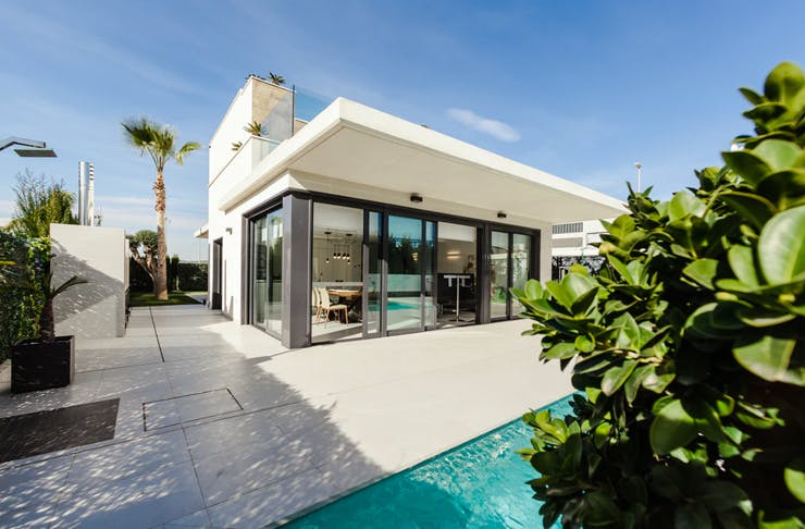 modern white mansion with tropical tiled backyard with pool and trees