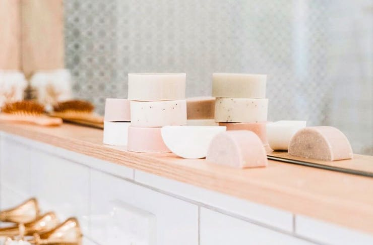 on a pale timber bench in a bathroom is a stack of shampoo bars