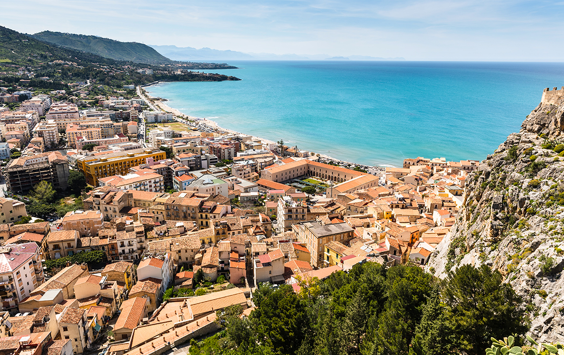 A aerial shot of Cefalù in Sicily, showing terracotta houses along a blue sea. In the background there are rolling, green mountains.