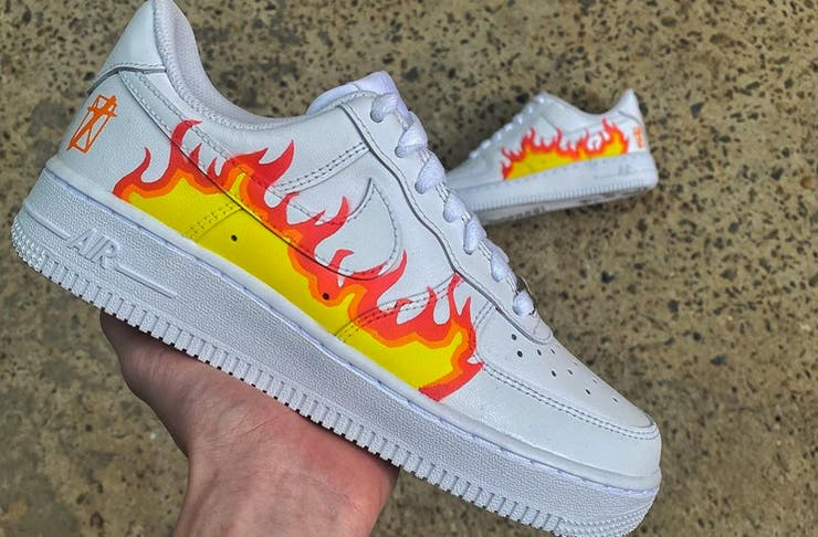 hand holding shoe with fire design