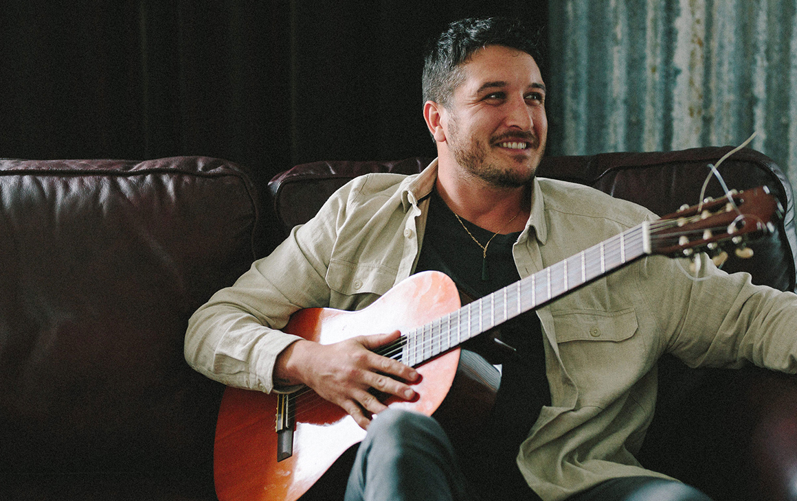 a man sitting on a couch with a guitar