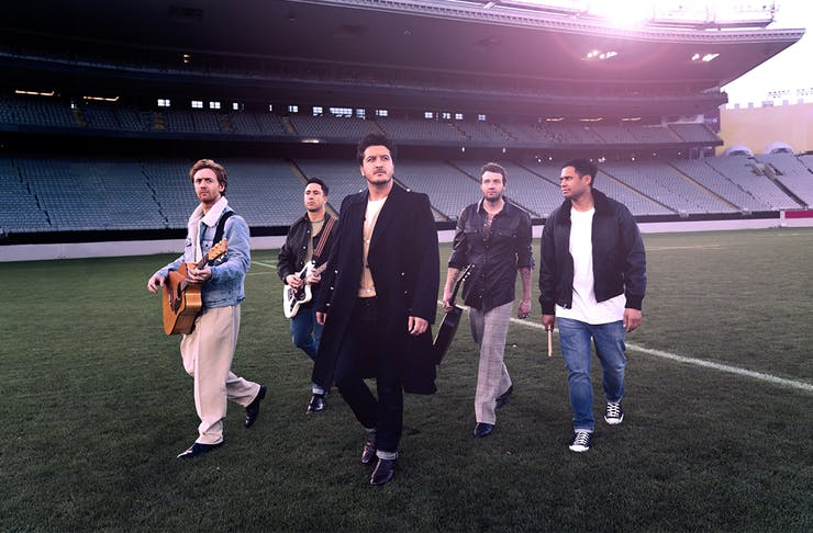 the band members of Six60 walking through a field