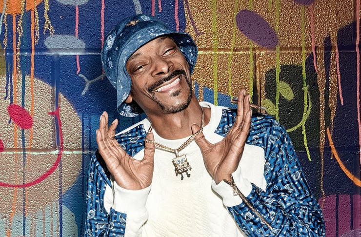 Snoop Dogg smiles, holding up his diamond necklace. He stands in front of a graffiti wall.