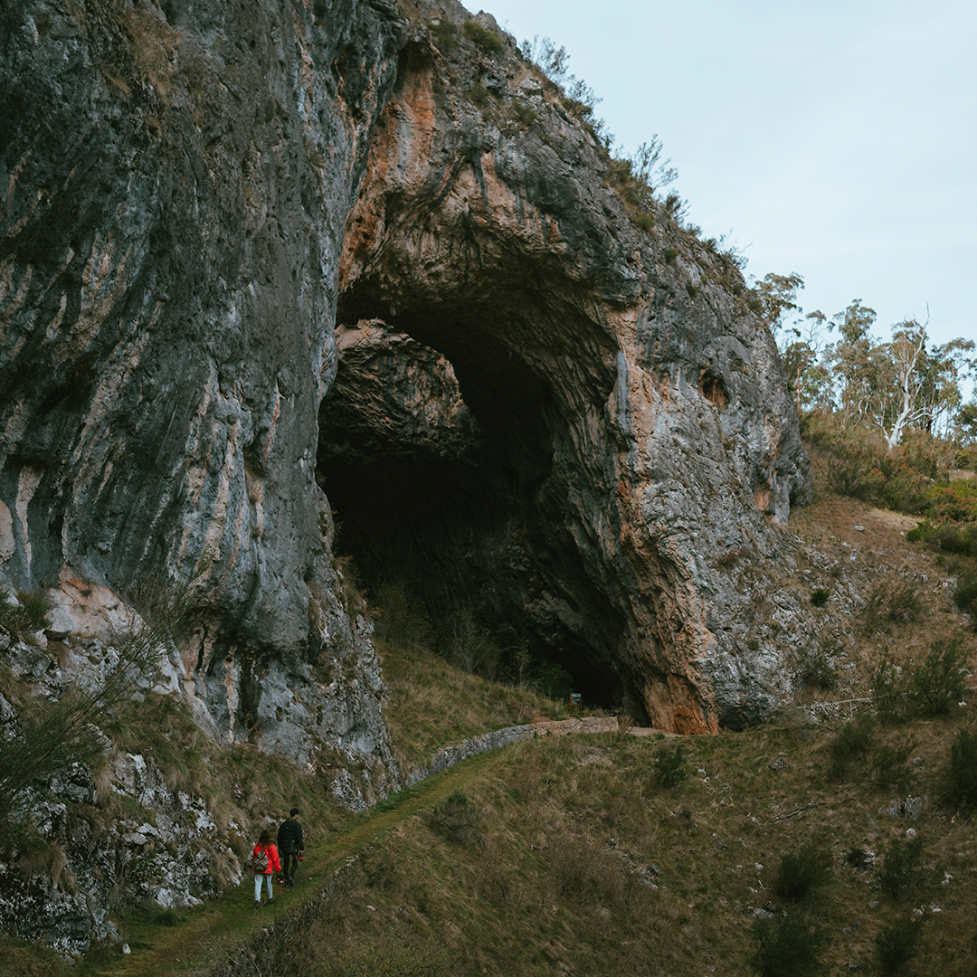 two people walking up mountain track into the south glory cave entrance