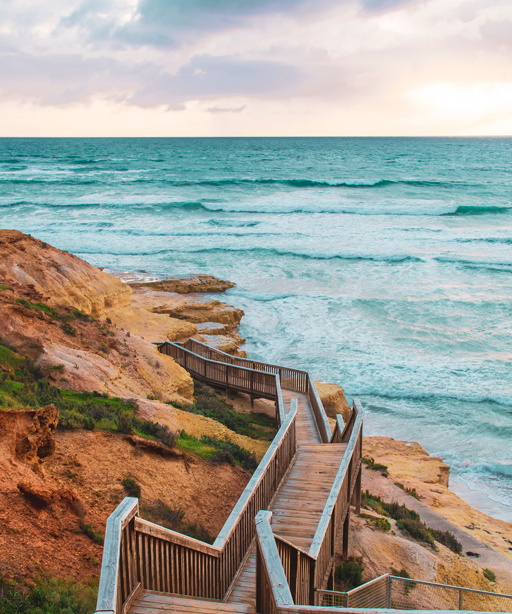 a set of stairs lead down to a beach at dusk.