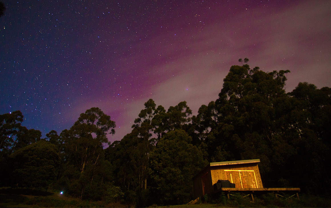 a small cabin at night, behind it a blanket of twinkling stars at night.