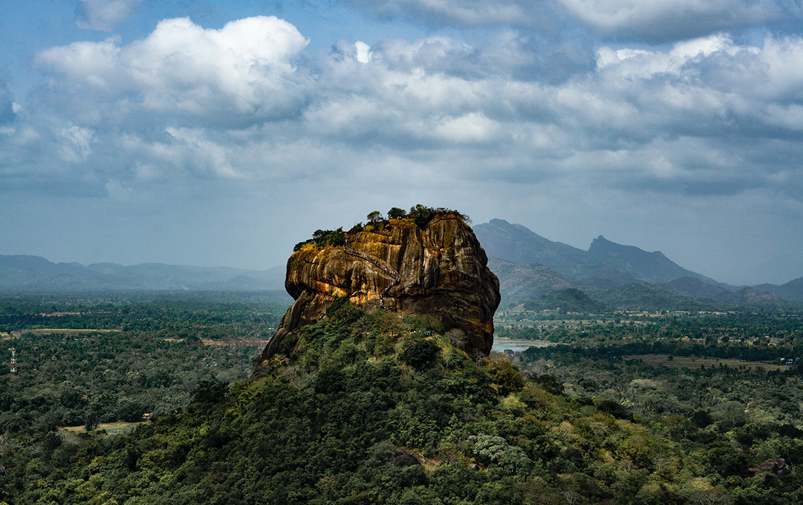 a large rocky formation stands out from clusters of trees in sri lanka