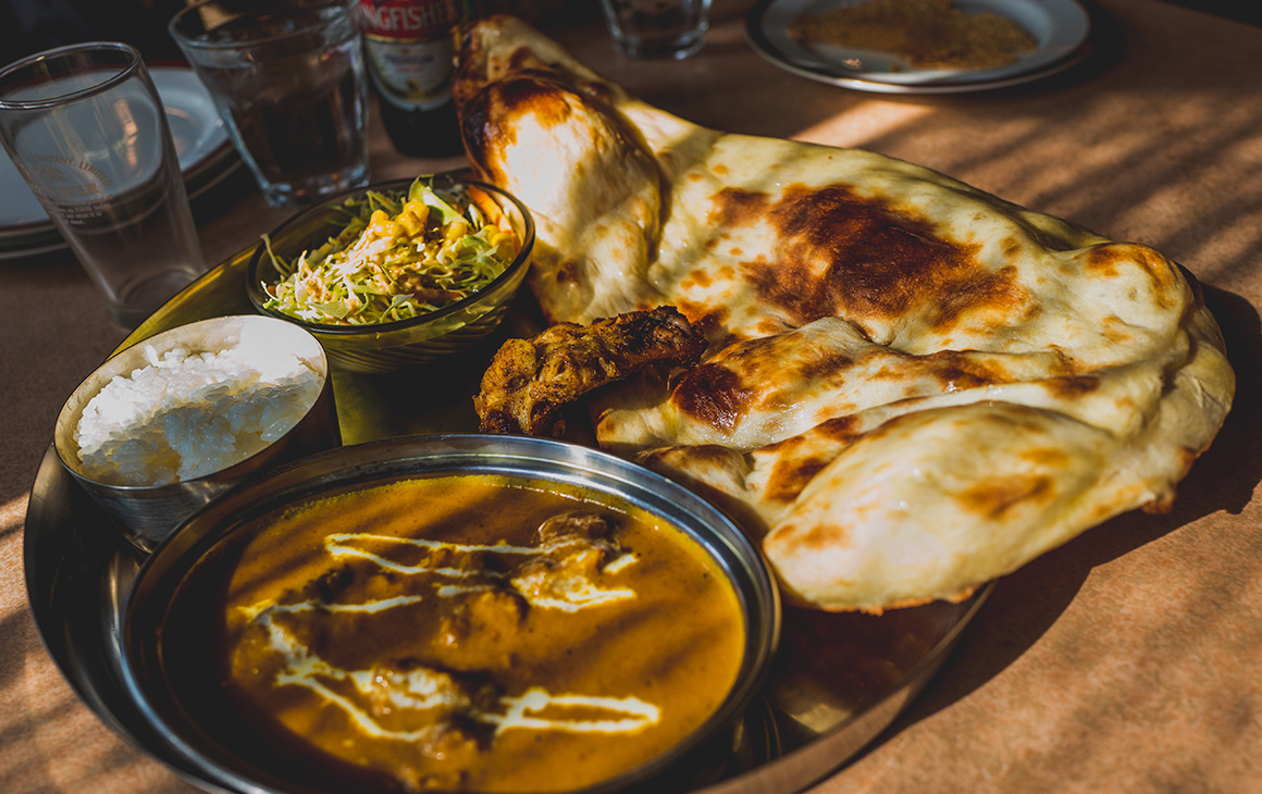 a curry, roti and drink sit on a tray in a cafe.