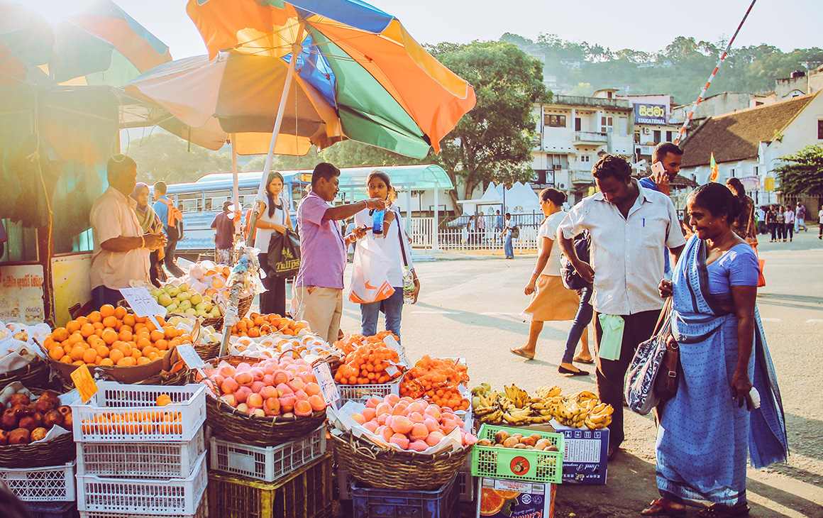 a group of Sri Lankan locals gather around a local market.