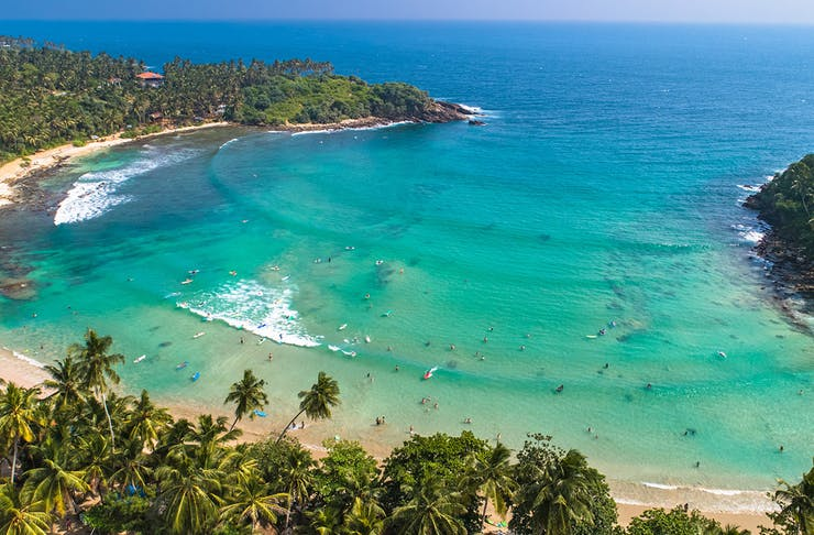a stunning blue and green beach is fringed by palm trees.