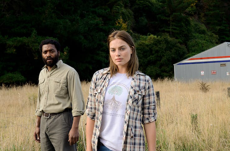 a young man and woman stands in a field of tall grass