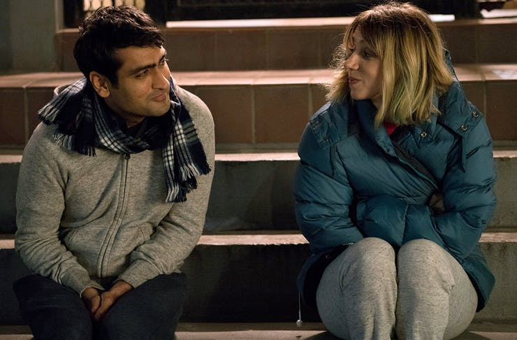 a man and woman look at each other while sitting on the steps