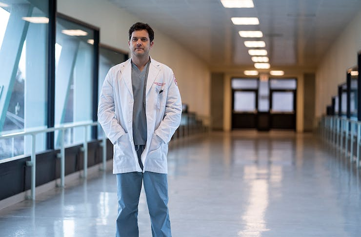 a man in a white doctors coat stands in the hallway of a hospital
