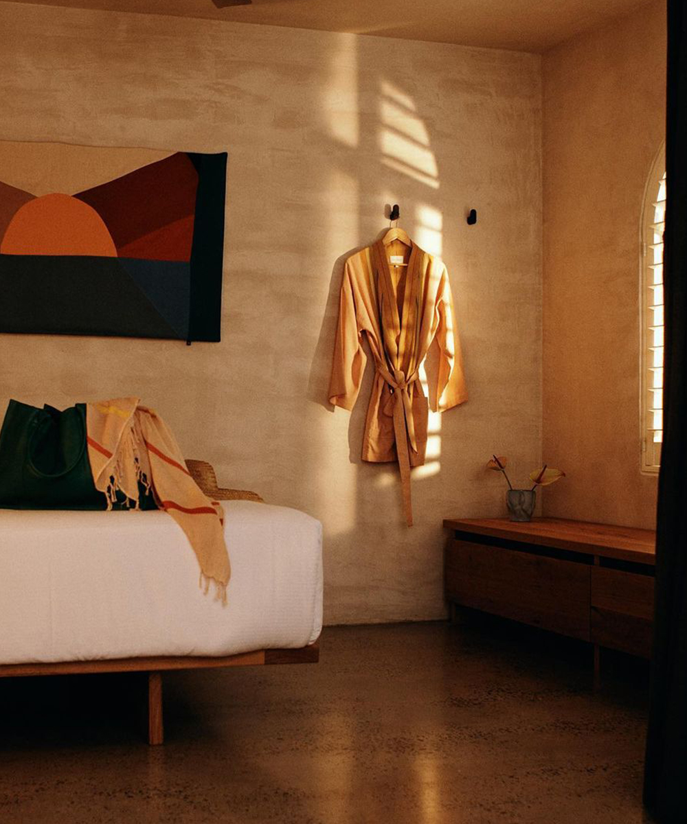 a bedroom at the Sunseeker motel. A bathrobe hangs on the wall.