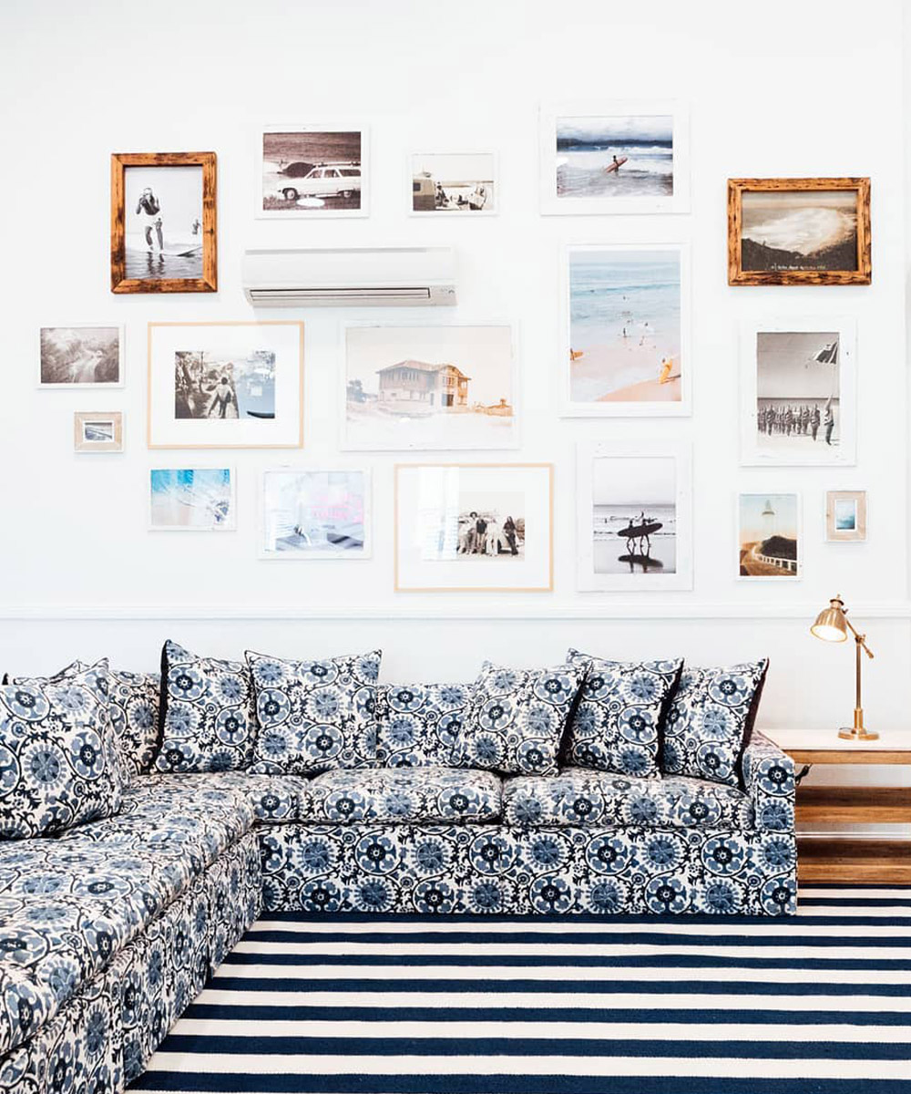 a blue and white printed couch against a wall full of picture frames