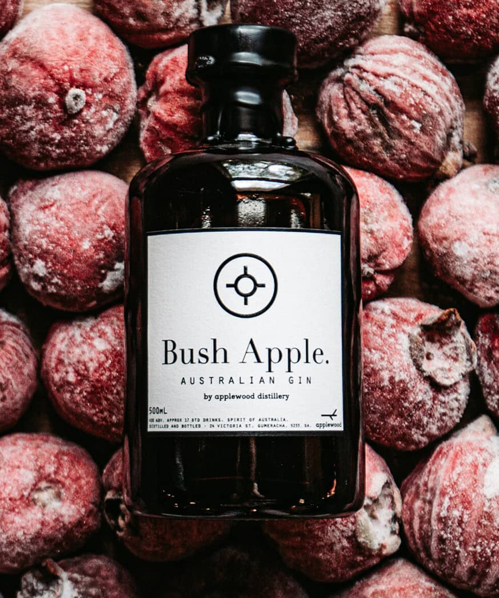 a bottle of gin sits on a background of bush apples