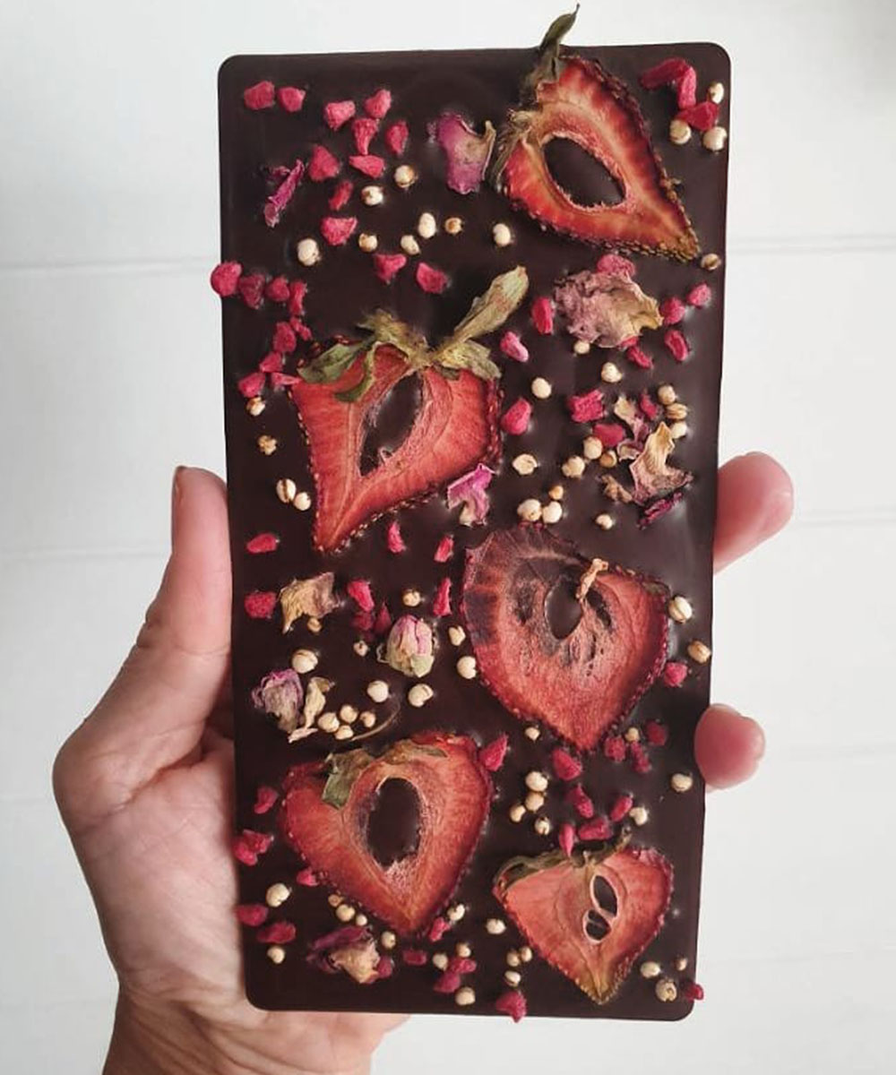 a slab of dark chocolate with flowers and berries in it.