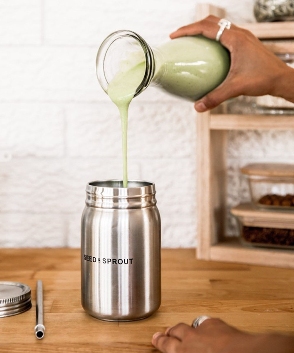 a green liquid is poured into a stainless steel cup