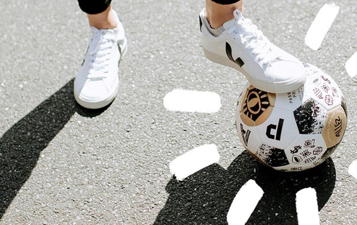 a man in a pair of white sneaker kicks a white soccer ball
