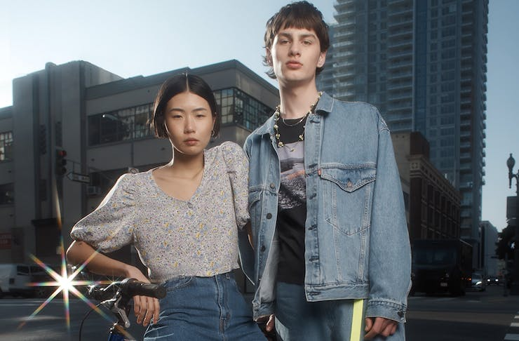 a young man and woman lean against a bike in a city.