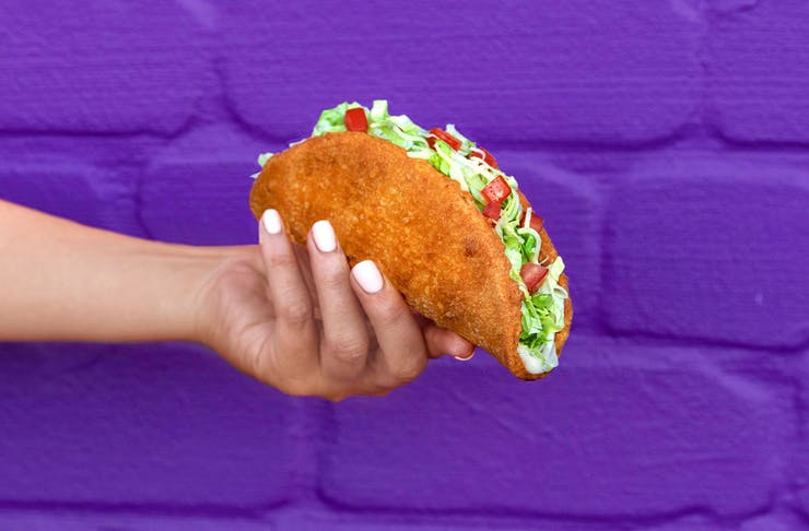 A hand holding the naked chicken taco in front of a purple wall