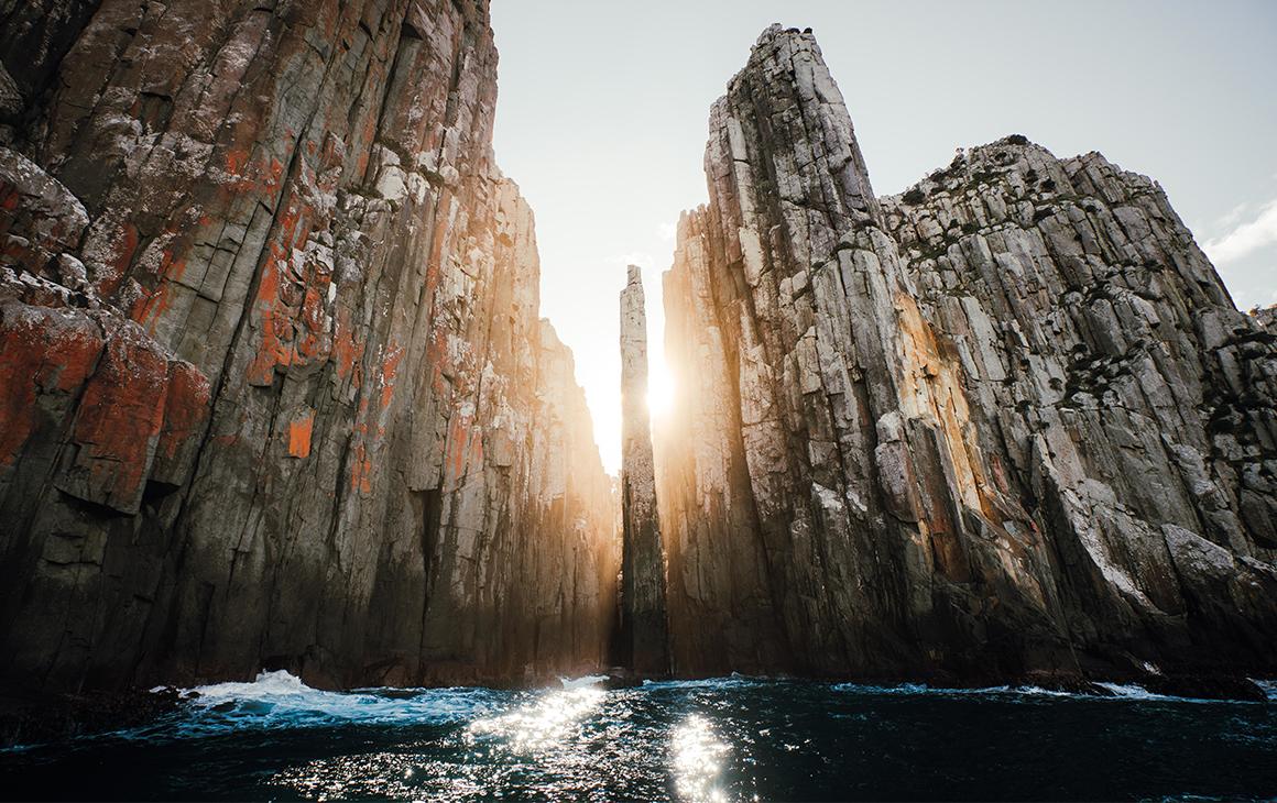 Sunlight streams through the towering cliffs at Tasman National Park