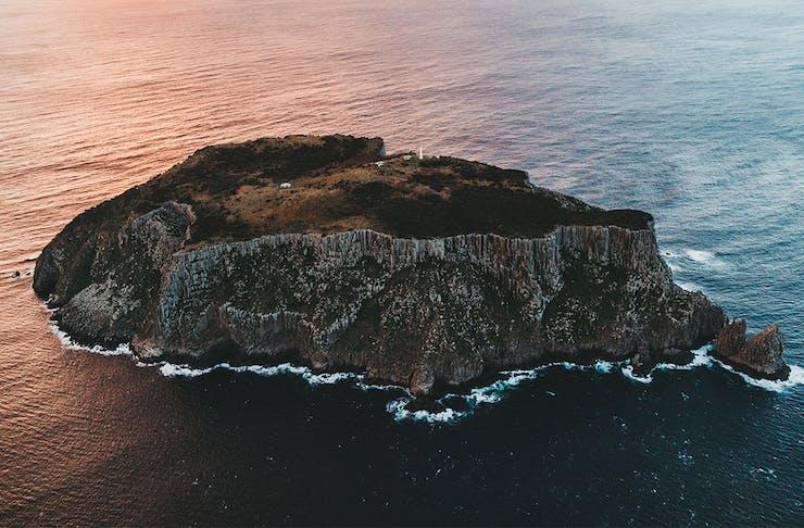 The ocean crashes against Tasman Island national ark at dusk.
