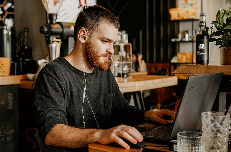 a young man wearing headphones types on a laptop in a cafe.