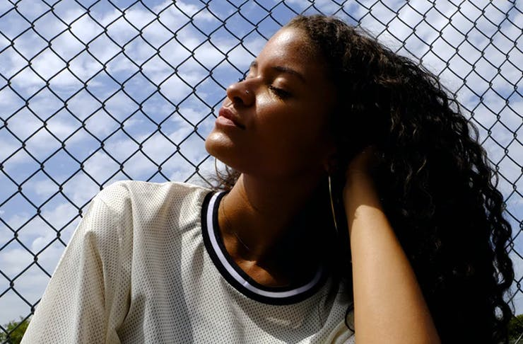 girl leaning on fence looking up at the sky