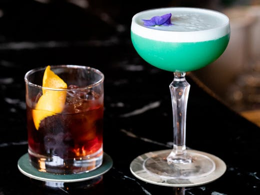 two cocktails sitting on top of marble bar top