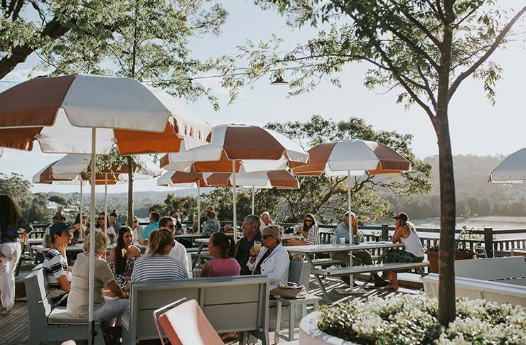 people sitting at outdoor dining tables with umbrellas at sunset