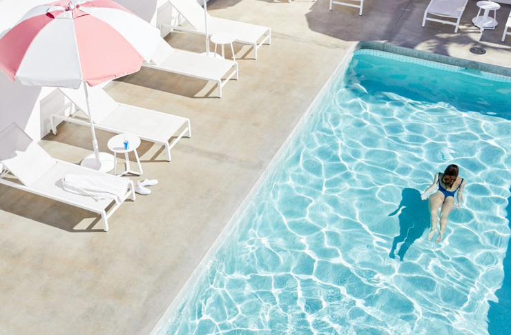 girl swimming underwater in retro pool surrounded by umbrellas