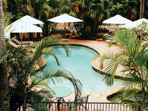 retro kidney shaped pool surrounded by tropical trees