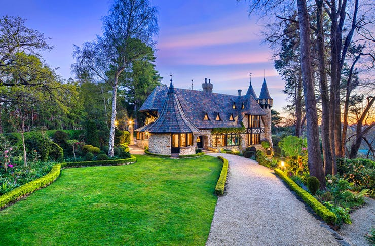 english style castle with huge front garden at sunset