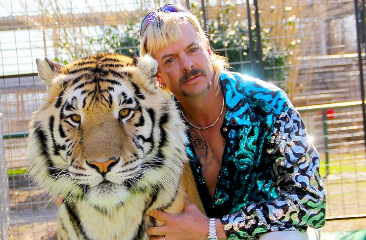 Tiger King, Joe Exotic, wears a blue shirt and cuddles up to a real tiger.