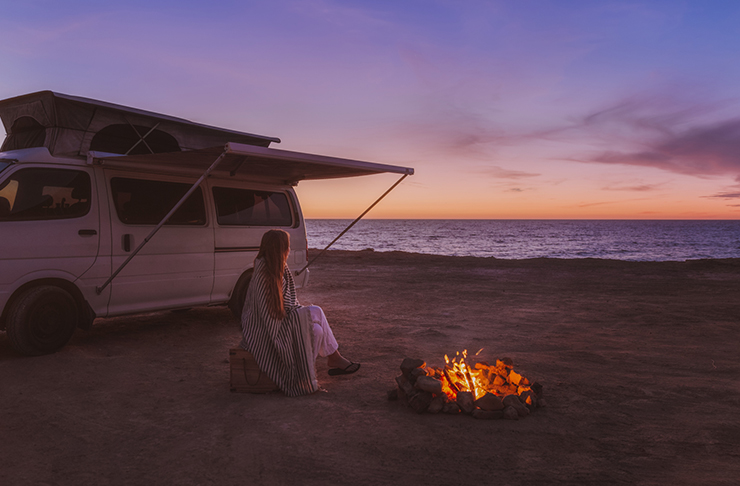 girl sitting on beach with van and fire at sunset