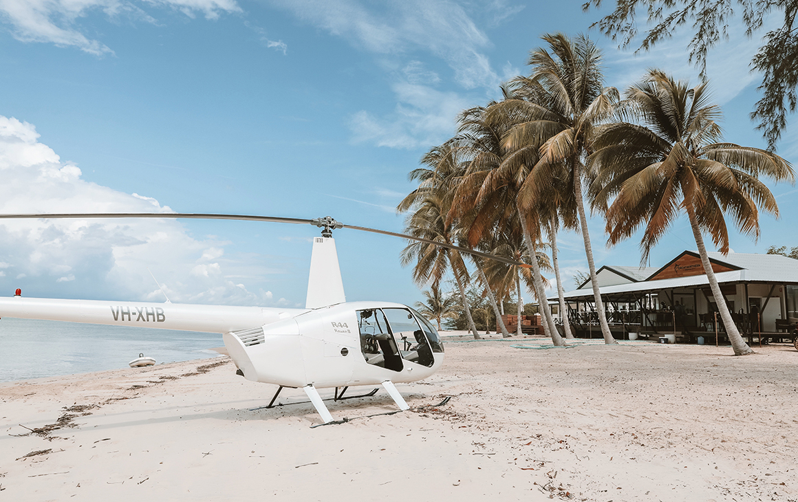 a white helicopter sits on a sandy beach outside the Tiwi Islands Retreat