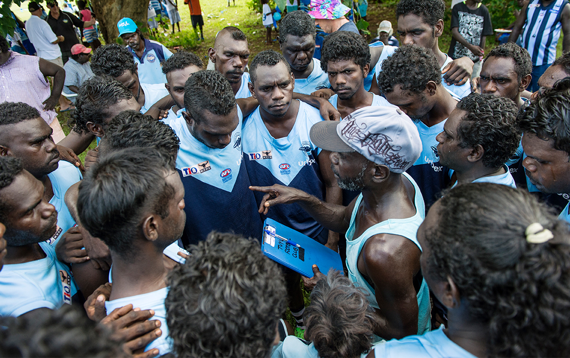 a cluster of AFL players huddle together ahead of the Tiwi Islands final